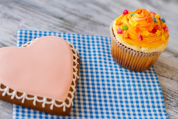 Cupcake à l'orange et confiserie de biscuits coeur sur une serviette délicieuse surprise pour la beauté des êtres...
