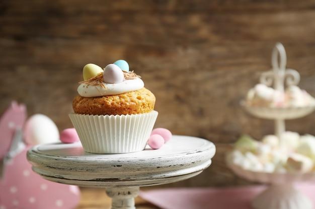 Cupcake de pâques savoureux sur le stand de gâteau contre la table en bois
