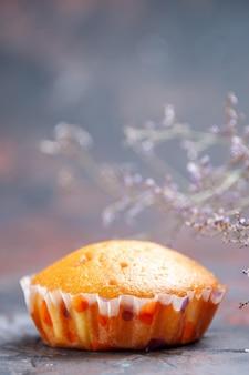 Cupcake vue latérale un cupcake appétissant sur le fond violet et les branches d'arbres
