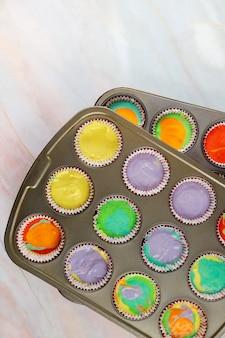 Cupcakes arc-en-ciel non cuits sur la plaque du four. vue de dessus.