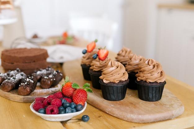 Cupcakes au caramel au chocolat sur planche de bois, baies sur assiette, génoise, gâteau aux pommes de terre sur la table