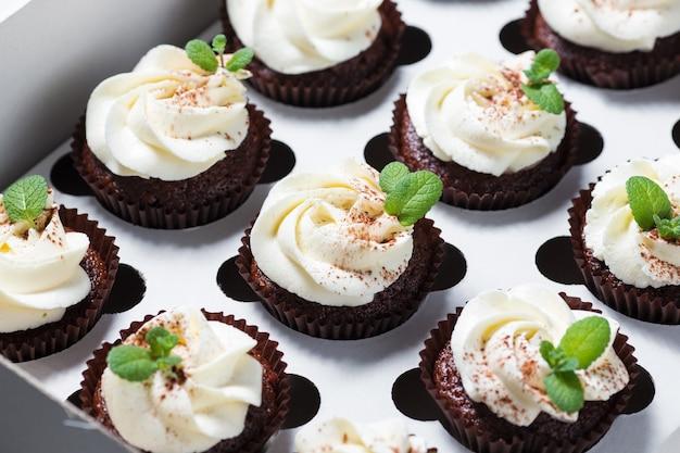 Cupcakes au chocolat avec crème au fromage et feuilles de menthe dans une boîte de livraison