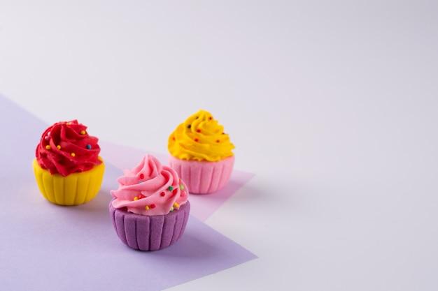 Cupcakes au sucre multicolores décoratifs sur fond clair avec des paillettes