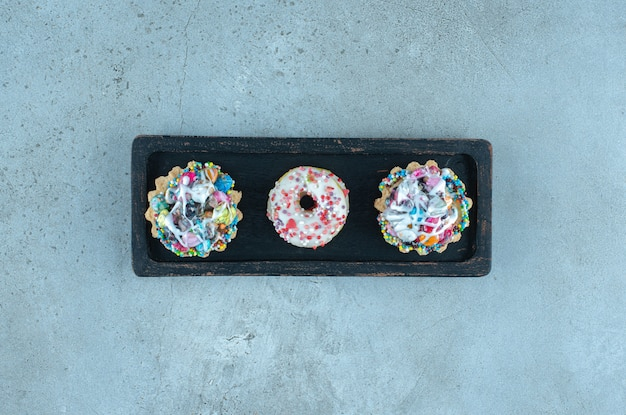 Cupcakes et beignets garnis de bonbons sur un plateau noir sur une surface en marbre