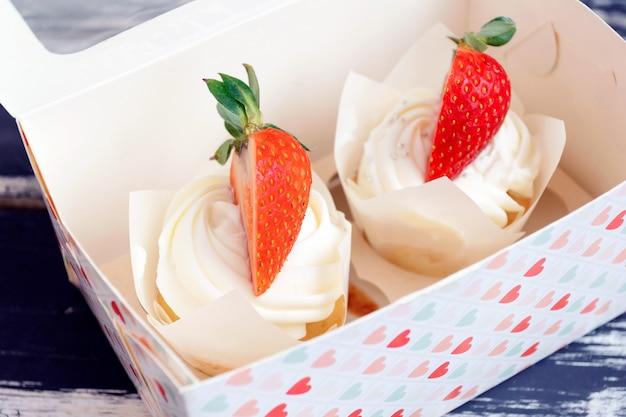 Cupcakes à la crème fouettée et fraises et myrtilles. concept d'amour, saint valentin.
