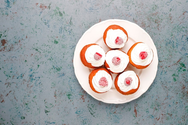 Cupcakes décorés de crème fouettée et de framboises surgelées.
