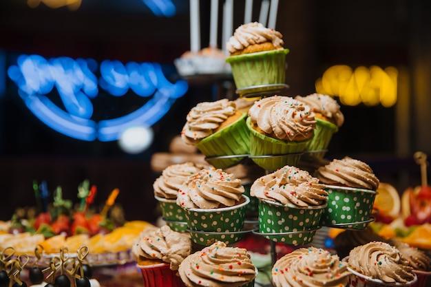 Des cupcakes fraîchement préparés se tiennent sur un support.