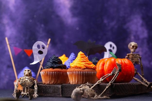 Cupcakes d'halloween avec crème et décor noir, violet et orange