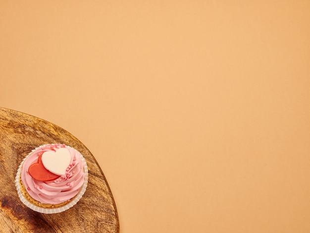 Cupcakes roses gâteaux avec coeurs sur une planche de bois de cuisine sur un fond marron beige