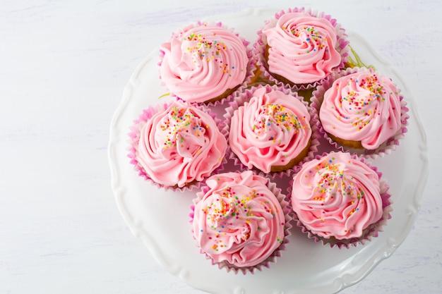 Cupcakes roses sur le stand de gâteau vue de dessus