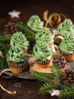Cupcakes de sapin de noël dessert sucré avec des paillettes d'or sur fond en bois avec guirlande lumineuse bokeh. fermer.
