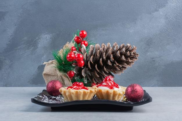 Cupcakes avec sauce aux fraises sur un plateau noir, livré avec des ornements de noël sur une surface en marbre