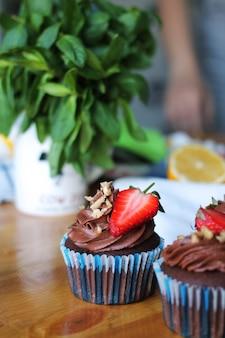 Cupcakes savoureux avec fraise et crème au chocolat