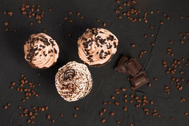 Cupcakes savoureux avec des pépites de chocolat sur fond noir