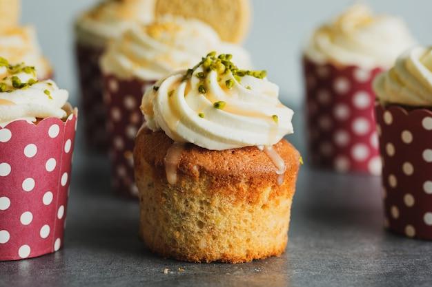 Cupcakes à la vanille avec crème et caramel sur fond de table gris.