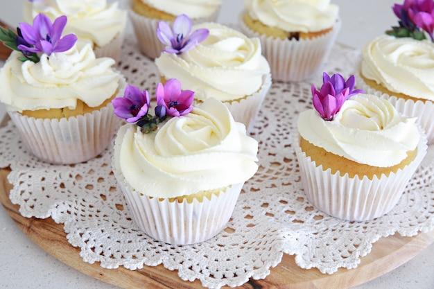 Cupcakes vanille glaçage à la fleur rose avec des fleurs comestibles violettes