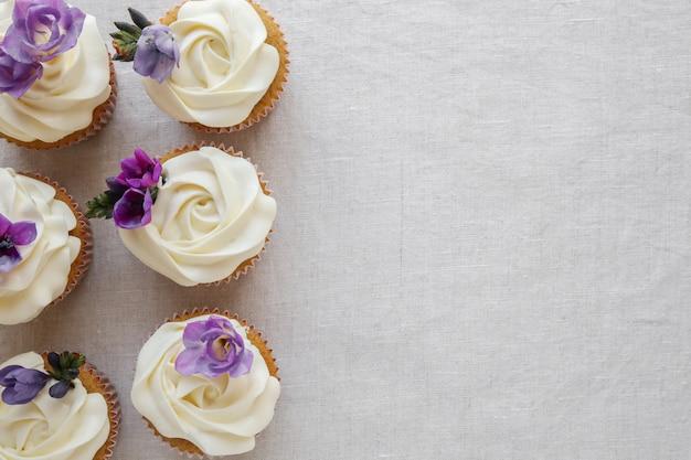 Cupcakes à la vanille et glaçage à la fleur de rose avec fleurs pourpres comestibles