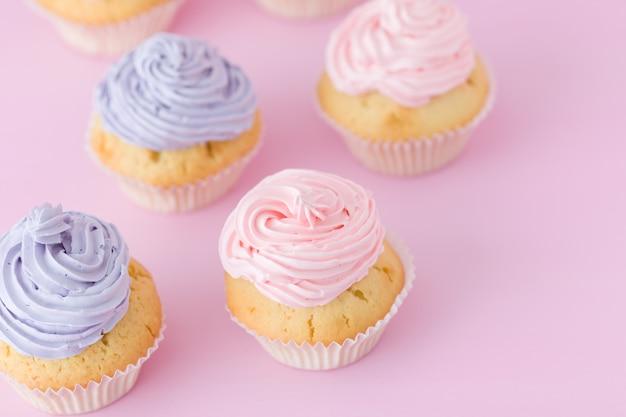Cupcakes violettes et roses avec crème au beurre, debout sur un fond rose pastel.
