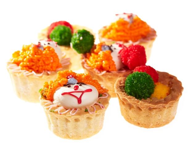 Cupcakes avec des visages souriants isolés sur blanc.