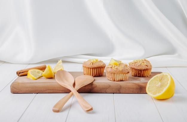 Cupcakes vue de face avec du citron et de la cannelle sur une planche avec des cuillères en bois sur une surface blanche