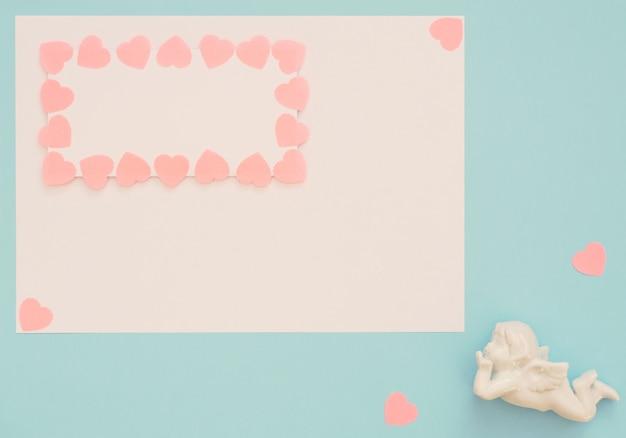 Cupidon blanc et feuille vierge avec cadre coeurs roses sur fond bleu
