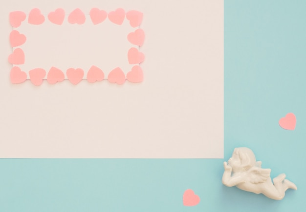 Cupidon blanc, feuille vierge avec cadre coeurs roses sur fond bleu.