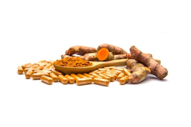 Curcuma cru, poudre dans une cuillère en bois et des capsules.