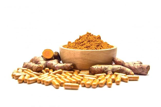 Curcuma cru, poudre dans une tasse en bois et des capsules.