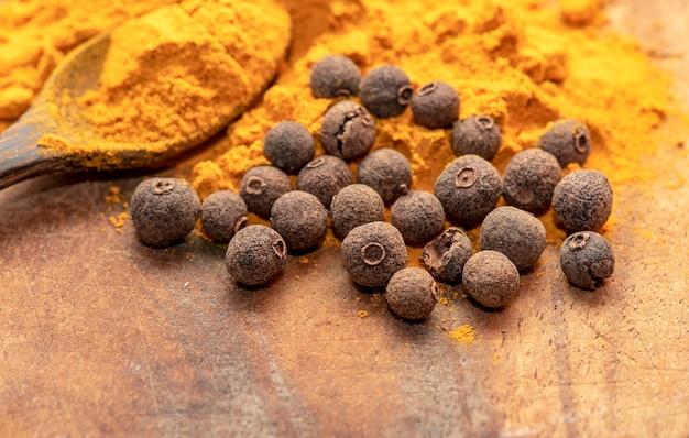 Curcuma indien ou curcuma avec du poivre et une cuillère sur une table en bois