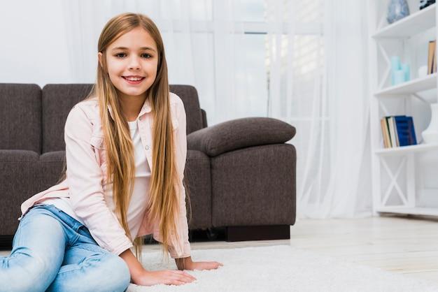 Cure fille souriante assise sur un tapis blanc à la recherche d'appareil photo