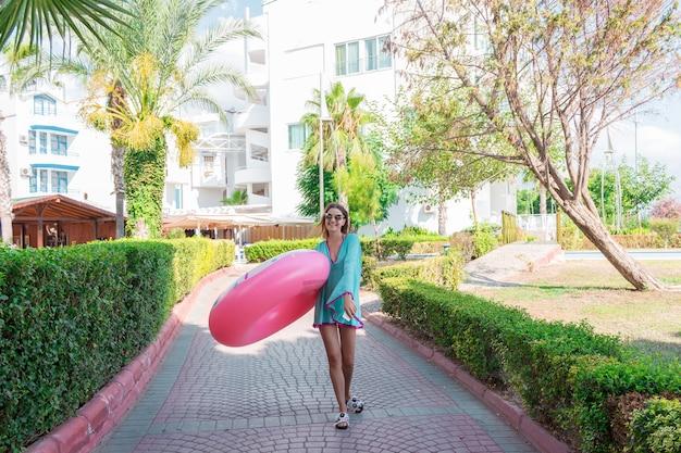 Cure girl va à la plage avec un cercle gonflable et écoute de la musique au casque sur son téléphone