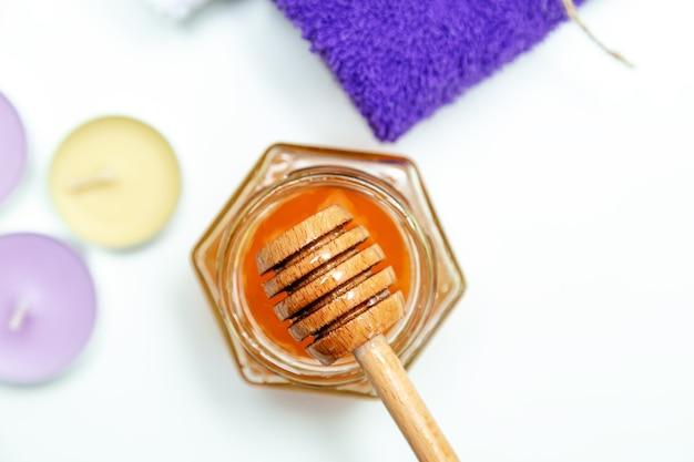 Cure thermale au miel. miel d'or dans un pot, fleurs d'orchidées, serviettes et bougies parfumées. soins naturels de la peau à domicile. fond blanc, vue de dessus.