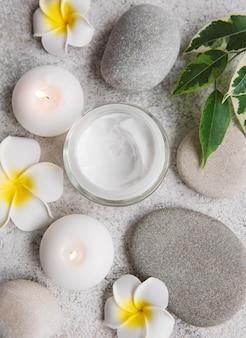 Cure thermale avec pierres de massage et crème hydratante sur fond de béton gris