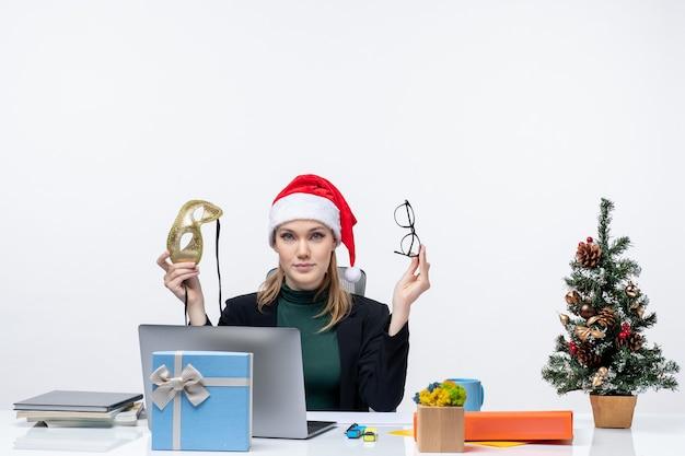 Curieuse belle femme avec des lunettes de chapeau de père noël et un masque assis à une table avec un arbre de noël et un cadeau dessus dans le bureau sur fond blanc