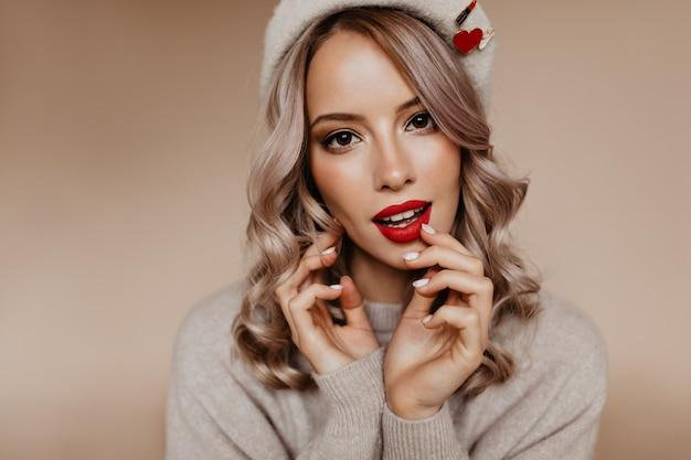 Curieuse femme aux yeux bruns avec des boucles blondes posant sur un mur marron