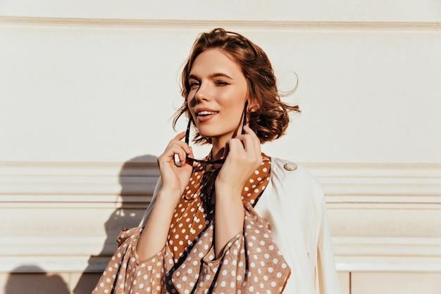 Curieuse femme brune avec un sourire doux. tir extérieur d'une jolie fille caucasienne tenant des lunettes de soleil.