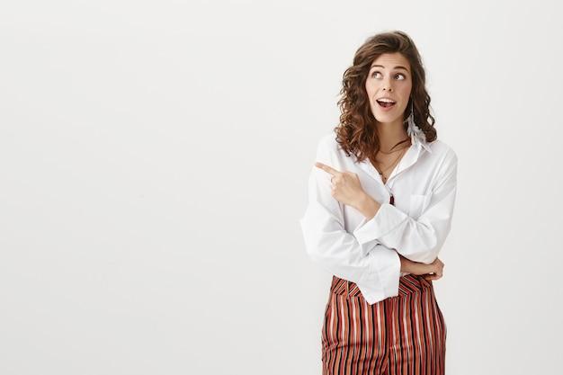 Curieuse femme entrepreneur attrayante regardant et pointant vers la gauche s'interroge