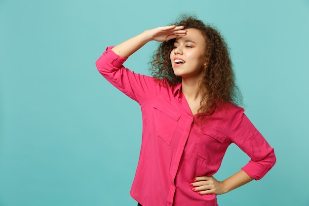 Curieuse fille africaine en vêtements décontractés roses tenant la main sur le front regardant au loin, distance isolée sur fond bleu turquoise. les gens émotions sincères, concept de style de vie. maquette de l'espace de copie.