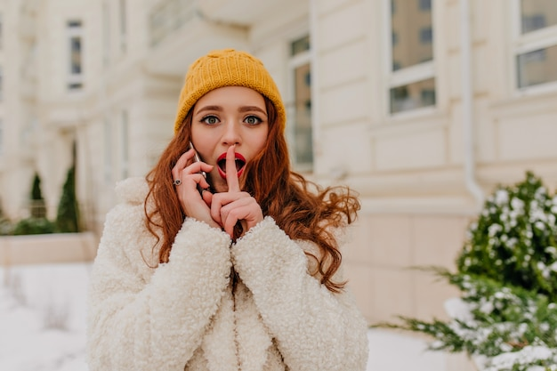 Curieuse fille rousse au chapeau, parler au téléphone en plein air. jolie jeune femme appelant quelqu'un.