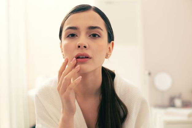 Curieuse jeune femme aux cheveux longs touchant pensivement ses lèvres et regardant devant elle