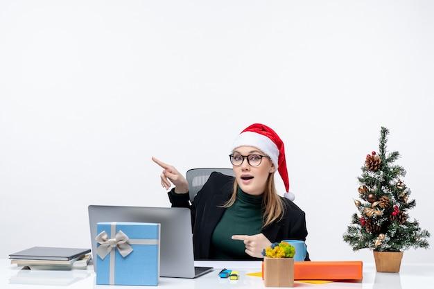 Curieuse jeune femme avec chapeau de père noël assis à une table avec un arbre de noël et un cadeau dessus et pointant au-dessus sur fond blanc