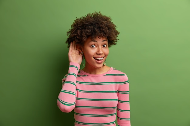 Curieuse jeune femme ethnique joyeuse tient la main près de l'oreille, écoute les rumeurs, surprend une conversation intéressante, aime connaître toutes les nouvelles, porte un pull rayé, pose sur un mur vert vif