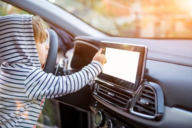 Curieuse petite fille tenant, touchant et tournant un bouton de lecteur à écran tactile mnultiedia de voiture. écran blanc vide