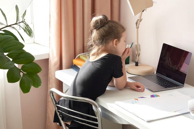 Curieuse petite fille utilisant un ordinateur portable au bureau