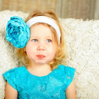 Curieux enfant fille souriante avec fleur bleue