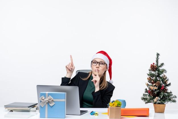 Curieux femme d'affaires avec chapeau de père noël assis à une table avec un arbre de noël et un cadeau dessus dans le bureau sur fond blanc