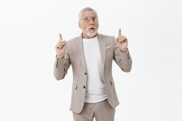 Curieux homme d'affaires senior en costume et lunettes pointant, regardant intrigué