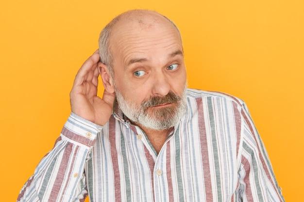 Curieux homme âgé snoopy avec barbe grise tenant la main à son oreille et haussant les sourcils, entendant. senior male ayant des problèmes d'audition, demandant à parler plus fort