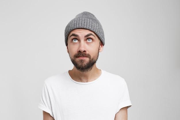 Curieux homme aux yeux bleus dans un chapeau gris regarde avec intérêt