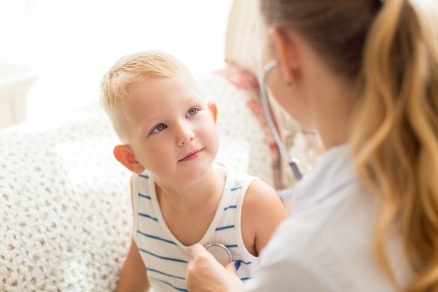 Curieux petit garçon en regardant une femme médecin
